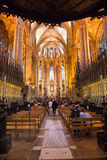 Barcelona Cathedral Looking Down Aisle Toward Apse. Looking Down Aisle Towards Apse in Barcelona Cathedral - Interior of Barcelona Cathedral with People Sitting Royalty Free Stock Photo