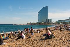 Barcelona city beach, tourists enjoy sea view. BARCELONA, CATALONIA, SPAIN, March, 2018: Barcelona city beach with people sunbathing and enjoying the sea view Stock Images