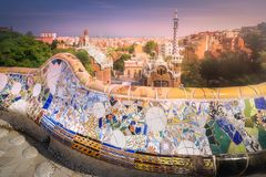 Barcelona cityscape in famous park Guell, Spain. View of mosaic tile and Barcelona cityscape in famous park Guell at summer sunset , Spain stock photography