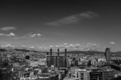 Barcelona downtown district, black and white urban scenery. Black and white view from Poble Sec district in Barcelona, clouds move over cityscape, mountains in stock photography