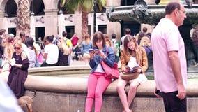 BARCELONA, ESPAÑA - ABRIL, 16, 2017 Dos mujeres jovenes que examinan las guías turísticas turísticas de la ciudad cerca de la fue almacen de metraje de vídeo