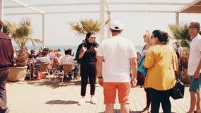 BARCELONA, ESPAÑA - ABRIL, 15, 2017 El steadicam largo tiró de gente en restaurante apretado de la playa vídeo 4K almacen de video