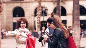BARCELONA, ESPAÑA - ABRIL, 16, 2017 Fotógrafo de la mujer que hace las fotos de la señal con su cámara de Nikon DSLR vídeo 4K almacen de video