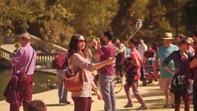 BARCELONA, ESPAÑA - ABRIL, 16, 2017 Mujer joven hermosa que hace el selfie con su teléfono y una barra en el parque contra almacen de video