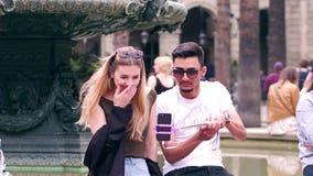 BARCELONA, ESPAÑA - ABRIL, 16, 2017 Pares jovenes interraciales hermosos que hacen selfies con un teléfono móvil y una barra cerc almacen de video