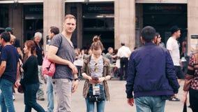 BARCELONA, ESPAÑA - ABRIL, 16, 2017 Pares jovenes que hacen las fotos de la calle y que usan el mapa turístico vídeo 4K almacen de metraje de vídeo
