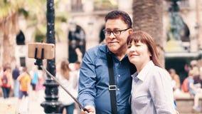 BARCELONA, ESPAÑA - ABRIL, 16, 2017 Pares maduros alegres que hacen el selfie con un teléfono celular y una barra vídeo 4K almacen de video