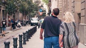 BARCELONA, ESPAÑA - ABRIL, 15, 2017 Steadicam tiró de los pares maduros que caminaban llevando a cabo las manos a lo largo de la  metrajes