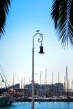 BARCELONA, ESPAÑA - 12 DE FEBRERO DE 2014: Una vista a un embarcadero con los yates, una gaviota que se sienta en una lámpara de  Fotos de archivo libres de regalías