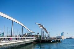 BARCELONA, ESPAÑA - 12 DE FEBRERO DE 2014: Una vista a un embarcadero con yates, un terraplén y una gaviota del vuelo en el puert Fotografía de archivo libre de regalías