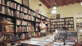Barcelona, España - septiembre de 2018: El hombre adulto está moviendo de un tirón las páginas de libros en una librería almacen de video