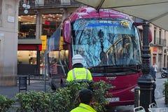 Barcelona, España 2 DE ENERO DE 2016 Un oficial de policía dice al conductor del autobús conducir con seguridad un cruce estrecho Imagen de archivo