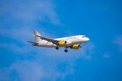 BARCELONA, ESPANHA - 20 DE AGOSTO DE 2016: O avião Vueling está voando sobre Barcelona Copie o espaço Fotos de Stock Royalty Free