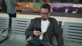 Barcelona, Espanha setembro de 2018 Homem nos vidros que sentam-se em uma Web surfando do banco no smartphone no metro de Barcelo vídeos de arquivo
