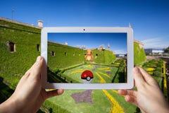 Barcelona Hiszpania, Lipiec, - 24: Androidu użytkownik przygotowywa łapać Pokemon Iść w sztuka zwiększającej rzeczywistości mobil Zdjęcie Stock