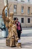Human statue and tourist at La Rambla in Barcelona Spain. BARCELONA - MARCH, 2018: Human statue and tourist at La Rambla in Barcelona Spain royalty free stock photo