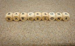 barcelona ord som byggs med träkuber och svarta bokstäver pÃ¥ golvet och botten av sandstranden fotografering för bildbyråer