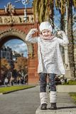 Child near Arc de Triomf in Barcelona, Spain showing strength. In Barcelona for a perfect winter. Full length portrait of happy trendy child near Arc de Triomf Royalty Free Stock Photography