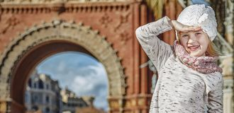 Girl near Arc de Triomf in Barcelona looking into distance. In Barcelona for a perfect winter. Full length portrait of happy trendy girl near Arc de Triomf in Stock Photos