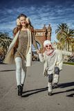 Mother and daughter near Arc de Triomf in Barcelona walking. In Barcelona for a perfect winter. Full length portrait of happy trendy mother and daughter near Arc Stock Photo