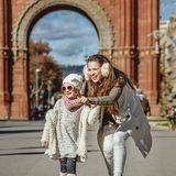 Mother pointing on something to child near Arc de Triomf. In Barcelona for a perfect winter. Full length portrait of happy trendy mother pointing on something to Stock Photo