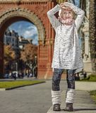 Smiling trendy child in Barcelona, Spain standing. In Barcelona for a perfect winter. Full length portrait of smiling trendy child in Barcelona, Spain standing Royalty Free Stock Photo