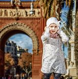 Girl near Arc de Triomf in Barcelona, Spain holding her hat. In Barcelona for a perfect winter. Full length portrait of trendy girl near Arc de Triomf in Stock Photo