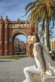 Elegant fashion-monger near Arc de Triomf sitting on parapet. In Barcelona for a perfect winter. happy elegant fashion-monger in earmuffs near Arc de Triomf in Royalty Free Stock Image