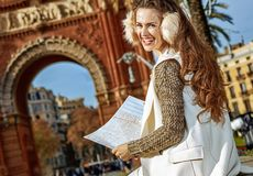 Happy woman near Arc de Triomf in Barcelona, Spain with map. In Barcelona for a perfect winter. happy modern woman in earmuffs near Arc de Triomf in Barcelona Stock Images