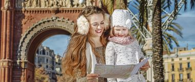 Mother and child near Arc de Triomf in Barcelona looking at map. In Barcelona for a perfect winter. happy young mother and child near Arc de Triomf in Barcelona Royalty Free Stock Image