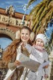 Mother and child near Arc de Triomf holding map and pointing. In Barcelona for a perfect winter. Portrait of happy modern mother and child near Arc de Triomf in Stock Photography