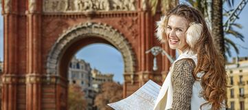 Happy woman near Arc de Triomf in Barcelona, Spain with map. In Barcelona for a perfect winter. Portrait of happy modern woman in earmuffs near Arc de Triomf in Stock Images