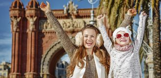 Mother and child near Arc de Triomf in Barcelona rejoicing. In Barcelona for a perfect winter. Portrait of happy trendy mother and child near Arc de Triomf in Royalty Free Stock Photography