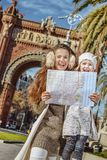 Mother and daughter near Arc de Triomf in Barcelona with map. In Barcelona for a perfect winter. Portrait of happy trendy mother and daughter near Arc de Triomf Royalty Free Stock Image