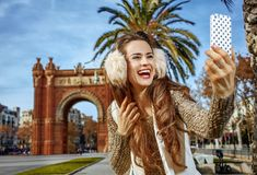 Woman near Arc de Triomf taking selfie with smartphone. In Barcelona for a perfect winter. Portrait of happy trendy woman in earmuffs near Arc de Triomf in Royalty Free Stock Photos