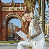 Smiling elegant woman in earmuffs in Barcelona, Spain with map. In Barcelona for a perfect winter. Portrait of smiling elegant woman in earmuffs in Barcelona Royalty Free Stock Image