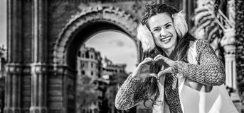 Fashion-monger near Arc de Triomf showing heart shaped hands. In Barcelona for a perfect winter. Portrait of smiling trendy fashion-monger in earmuffs near Arc Royalty Free Stock Images