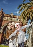 Mother and daughter near Arc de Triomf having fun time. In Barcelona for a perfect winter. Portrait of smiling trendy mother and daughter near Arc de Triomf in Royalty Free Stock Image