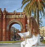 Woman near Arc de Triomf in Barcelona, Spain looking at map Royalty Free Stock Photo