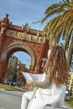 Woman near Arc de Triomf in Barcelona, Spain looking at map Royalty Free Stock Images