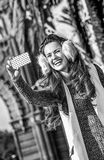 Fashion-monger near Arc de Triomf taking selfie with cellphone. In Barcelona for a perfect winter. smiling elegant fashion-monger in earmuffs near Arc de Triomf Royalty Free Stock Photos