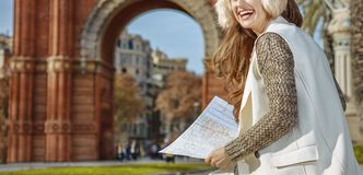 Woman near Arc de Triomf with map looking into distance Royalty Free Stock Photos