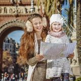 Mother and daughter near Arc de Triomf looking at map. In Barcelona for a perfect winter. smiling modern mother and daughter near Arc de Triomf in Barcelona Stock Images