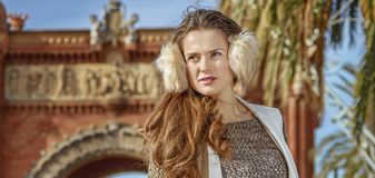 Woman near Arc de Triomf in Barcelona looking into distance. In Barcelona for a perfect winter. trendy woman in earmuffs near Arc de Triomf in Barcelona, Spain Stock Photography