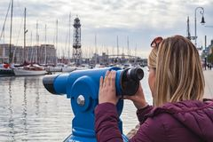 Barcelona port, seashore. Young blonde woman looking into binoculars at the port of Barcelona, Catalonia - seashore stock photos