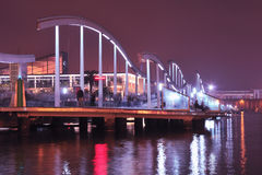 Barcelona Port Vell. Night image of scenic pedestrian walkway in Barcelona Port Vell area with walking people Stock Image