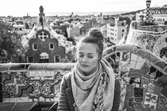 Woman listening audioguide while sitting on bench in Barcelona. Barcelona signature style. relaxed modern traveller woman in coat at Guell Park in Barcelona Stock Photos