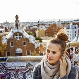 Woman in Barcelona listening audioguide while sitting on bench. Barcelona signature style. young tourist woman in coat in Barcelona, Spain listening audioguide Stock Images