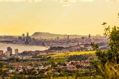 Barcelona skyline at dusk, seen from the north. Barcelona skyline with harbor, Mediterranean and Montjuich mountain stock photo