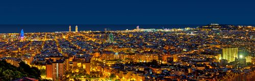 Barcelona skyline at night looking towards the sea. Showing emblematic buildings such as Agbar tower, Sagrada Familia, W hotel, Arts hotel and Montjuic castle royalty free stock image